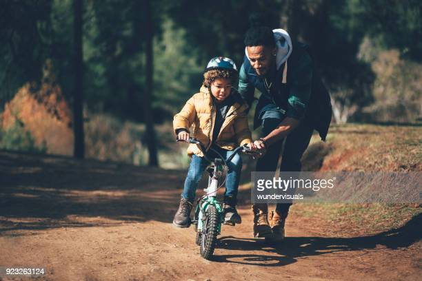 young father teaching son how to ride bicycle in park - bicycle stock photos and pictures
