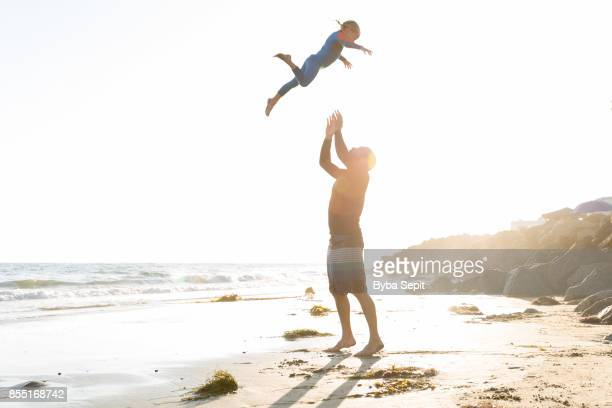 Young father throws his 5 year old daughter high in the air.