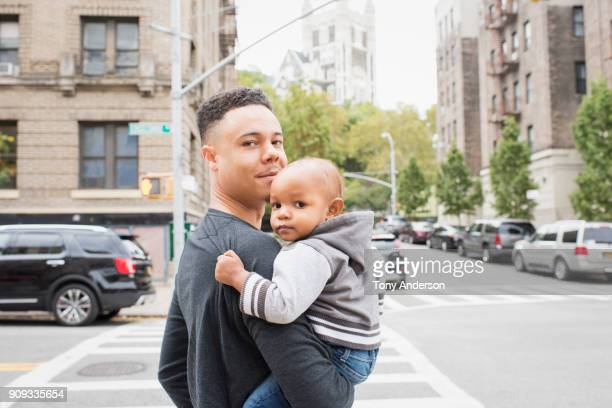 Young father walking with infant daughter in city neighborhood
