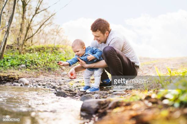young father with a toddler son playing outside. - time stock pictures, royalty-free photos & images