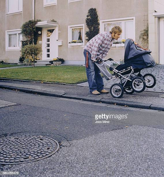Young Father with Baby Carriage on Sidewalk