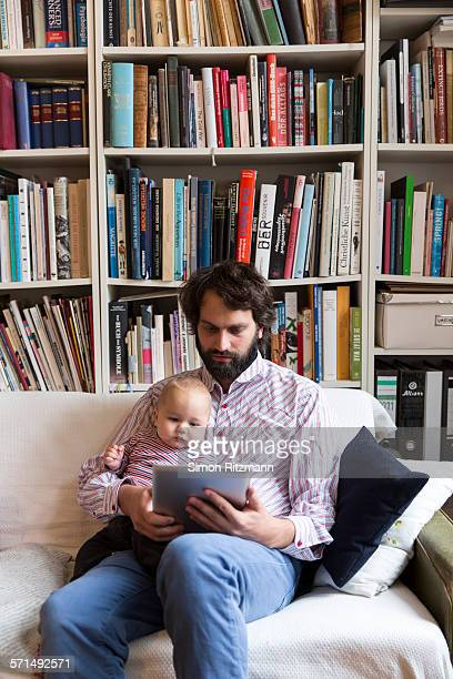 Young father with baby son using tablet computer