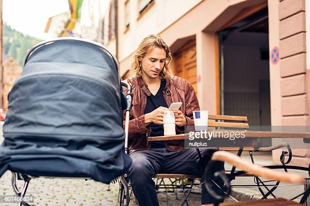 Young father with baby stroller having coffee at a cafe