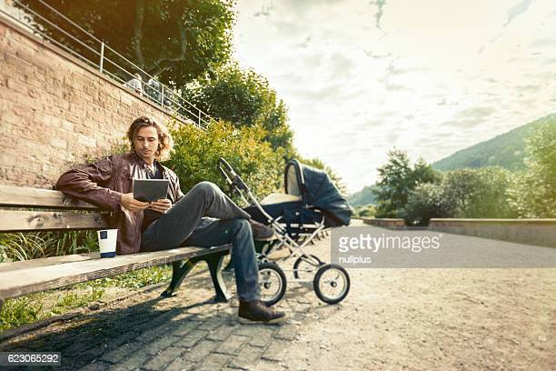 Young father with baby stroller in the park