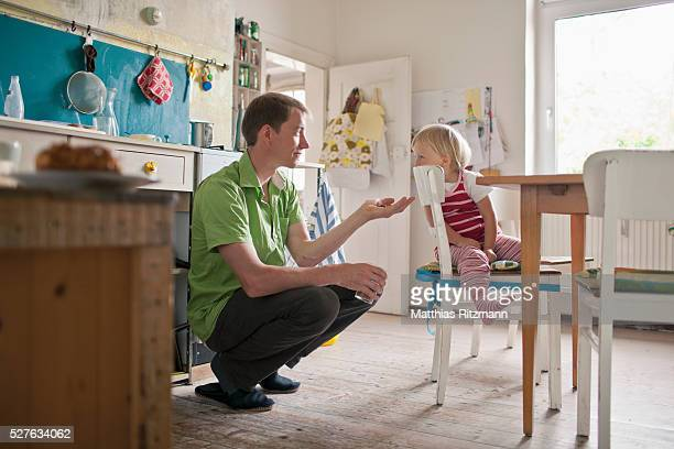 Young father with daughter (1-2) in kitchen