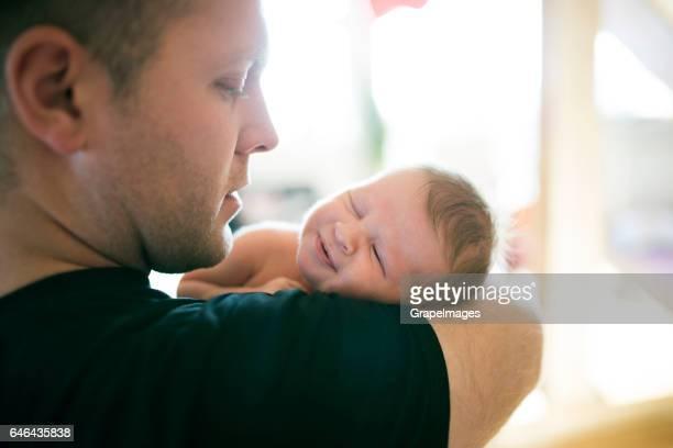 Jeune père avec sa fille nouveau-né dans ses bras
