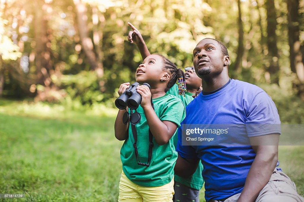 Young father with son and daughter bird watching in eco forest camp : Stock Photo
