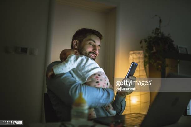 young father working at home with his baby  girl - night stock pictures, royalty-free photos & images
