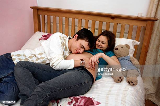 A young fathertobe lies on a bed beside his girlfriend and rests his head on her belly to feel their baby moving She is 15 years old one of Britain's...