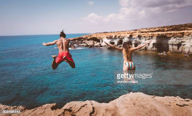 Young fearless divers couple jumping off cliff into ocean