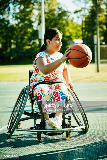 Young female adaptive athlete dribbling basketball on outdoor court on summer evening