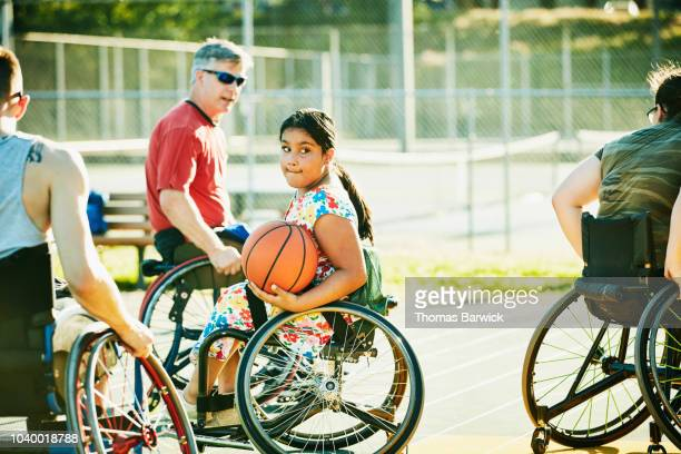 Young female adaptive athlete playing wheelchair basketball on summer evening