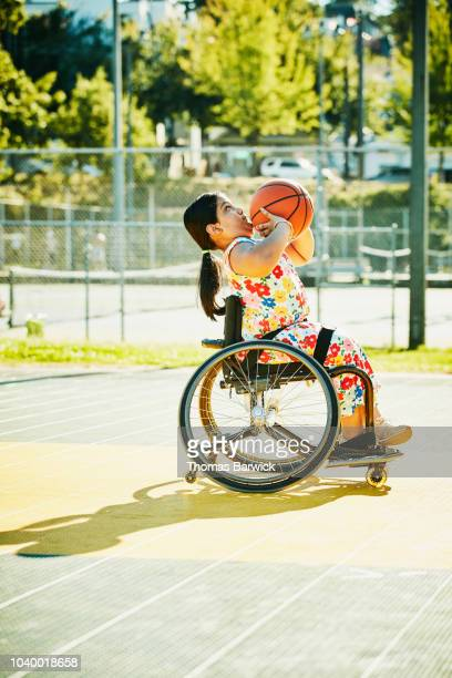 Young female adaptive athlete preparing to shoot basketball on outdoor court on summer evening