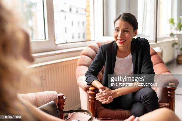 young female adult are talking with her co-worker - interview stock pictures, royalty-free photos & images