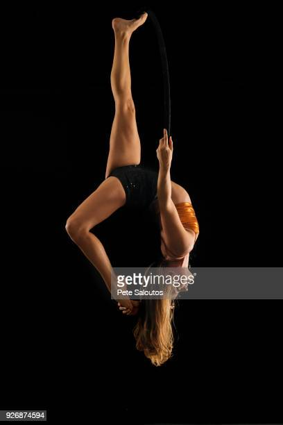 young female aerial acrobat hanging upside down from hoop against black background - 空中曲芸師 ストックフォトと画像