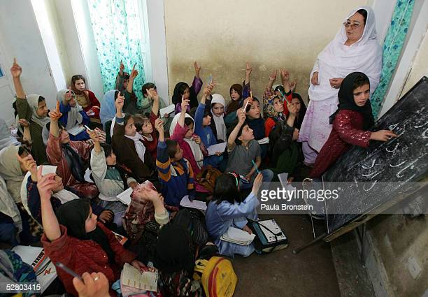 Young female Afghans raise their hands to take a turn at the bulletin board during a Dari language class at the Aschiana school for street children...
