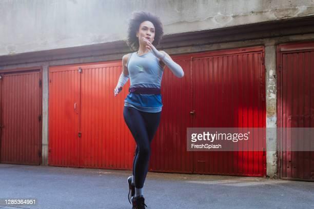 ガレージの列の隣で屋外を走る若い女性アフロアメリカのアスリート - ストラップ ストックフォトと画像