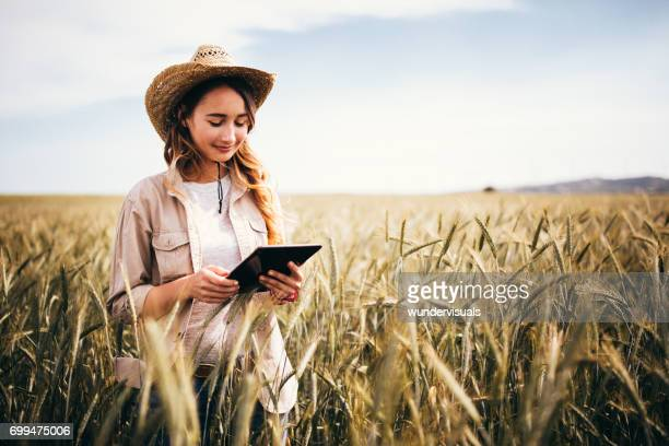 Young female agriculture scientist checking wheat crops with digital tablet