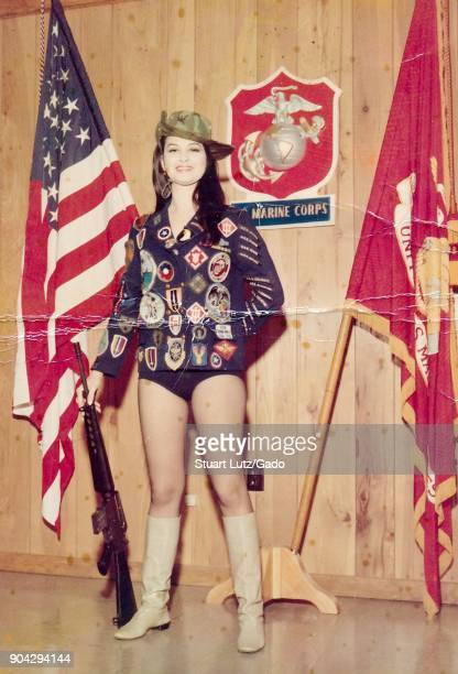 A young female American USO performer wearing suggestive clothing and a cowboy hat and boots with a jacket which has many colorful patches smiles and...