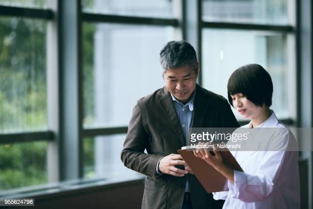 若い女性と中年男性のエンジニアのオフィス スペースの外会話します。