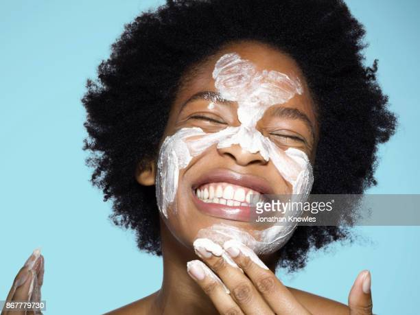 young female applying face cream / mask - indulgence stock pictures, royalty-free photos & images