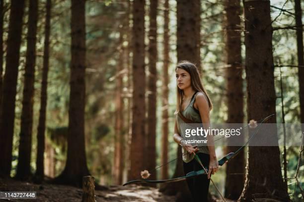 archer fêmea novo que pratica nas madeiras. caça fêmea do caçador na floresta por se durante. - arco arco e flecha - fotografias e filmes do acervo
