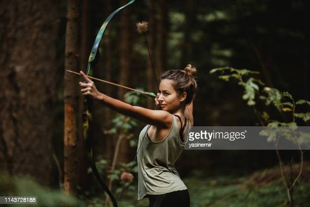 young female archer practicing in the woods. female hunter hunting in the forest by herself during the. - archery stock pictures, royalty-free photos & images
