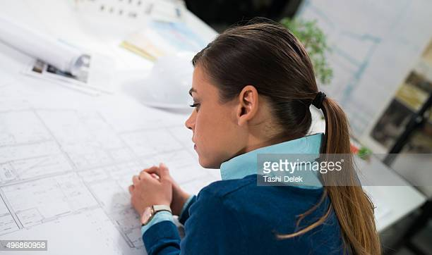 Young Female Architect Looking At Blueprint