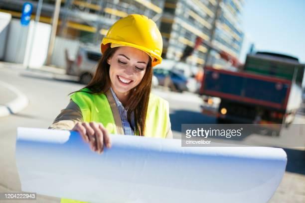 joven arquitecta en el sitio de consturction mirando el plano - ingeniero civil fotografías e imágenes de stock