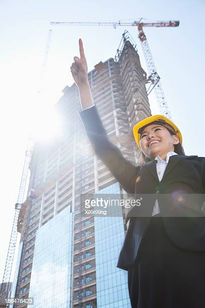 Young female architect pointing at a construction site