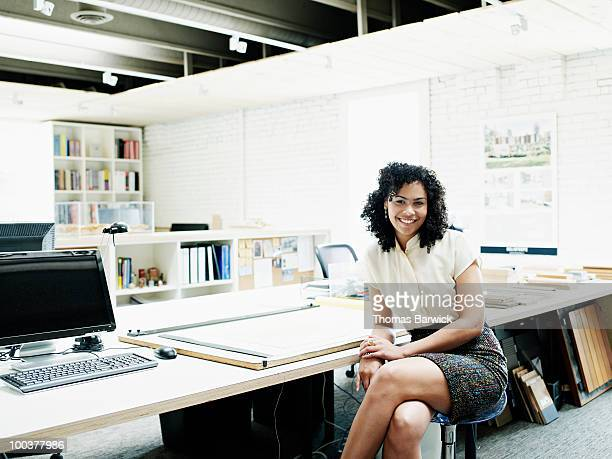 Young female architect sitting at desk in office