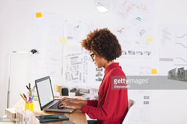 Young female architect using laptop at her office