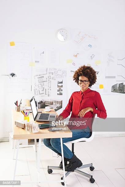 Young female architect with laptop at her desk
