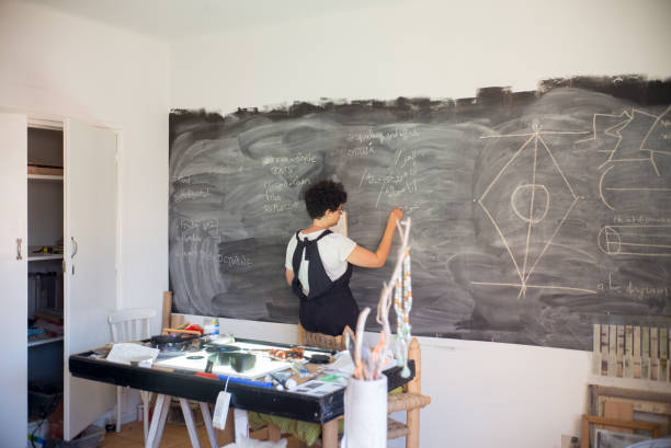 young female artist drawing on a chalkboard in her studio