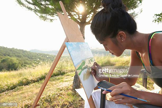 Young female artist painting landscape, Buonconvento, Tuscany, Italy