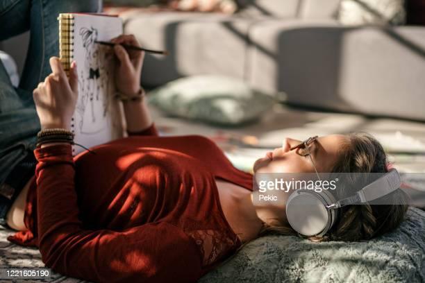 若い女性アーティストのリラックスとドローイング - 外出禁止令 ストックフォトと画像