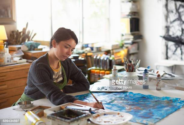 A young female artist working in her studio
