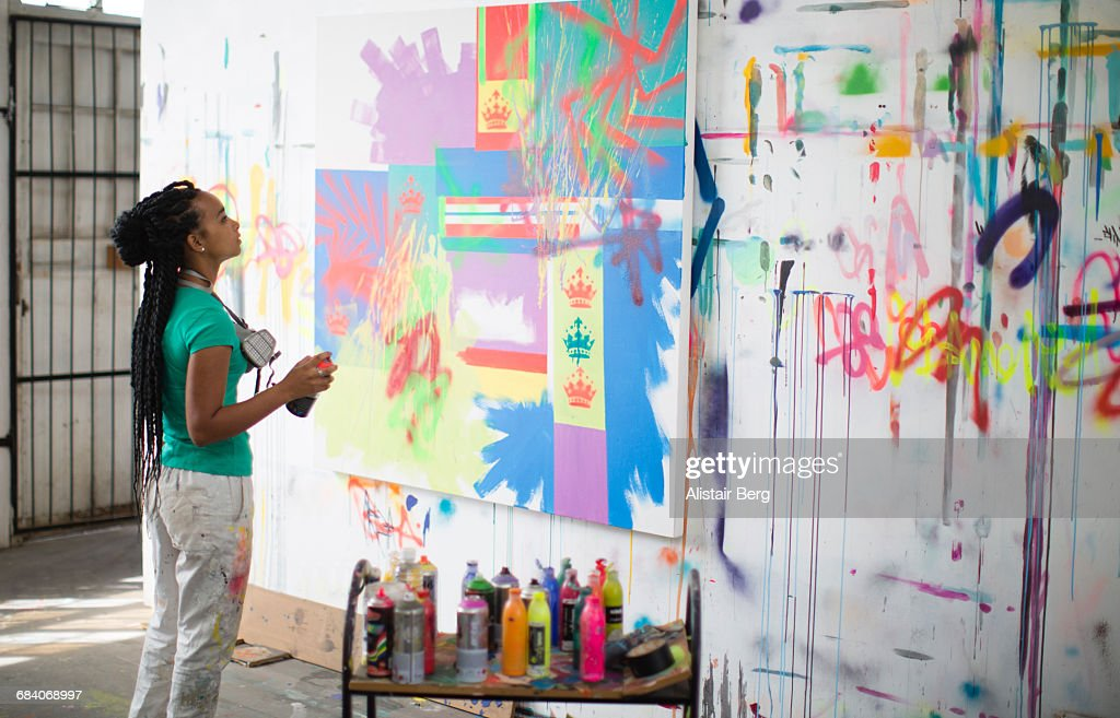 Young female artist working in her studio : Stock Photo