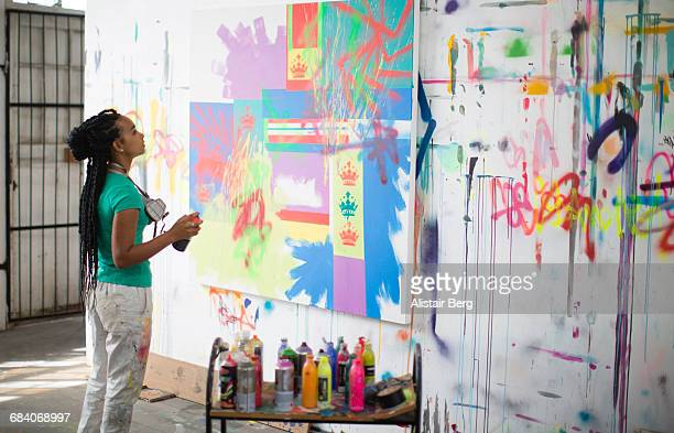 young female artist working in her studio - graffiti foto e immagini stock