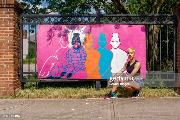a young female artists sits proudly in front of her street painting - columbus ohio stock pictures, royalty-free photos & images