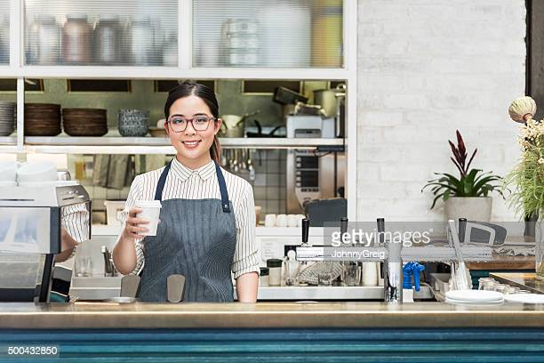 Young female Asian barista holding coffee at cafe counter