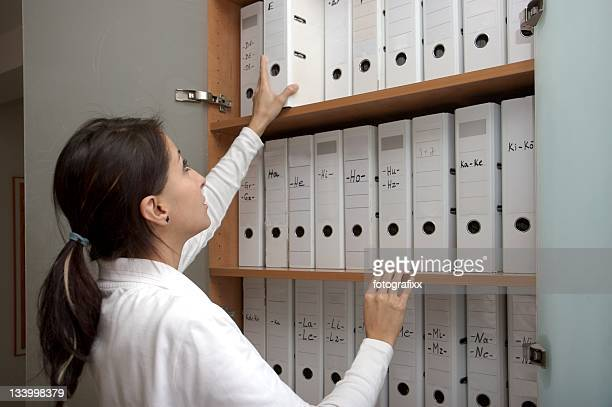 young female assistant looks for folders into a doctor's office