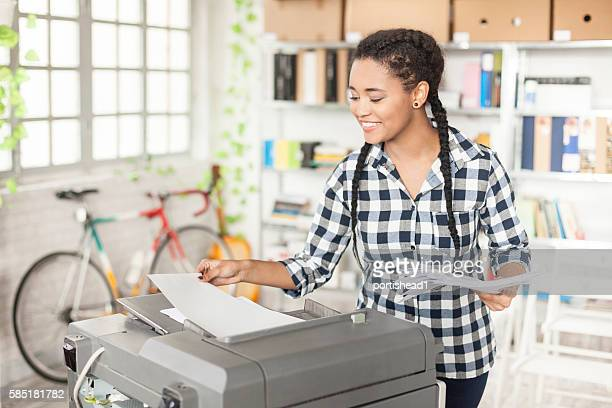 young female assistant using copy machine at workplace - printing out stock pictures, royalty-free photos & images