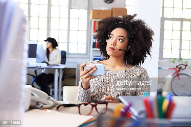 Young female assistant using smart phone at work