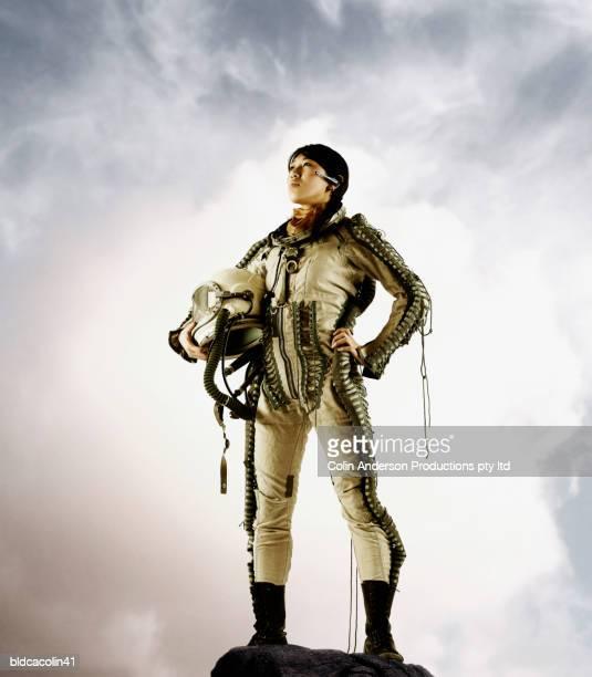 young female astronaut holding a space helmet - traje espacial fotografías e imágenes de stock