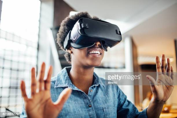 Young female at startup using VR goggles