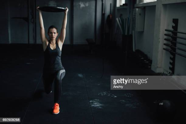 young female at the gym trains with heavy weights - snatch weightlifting stock photos and pictures