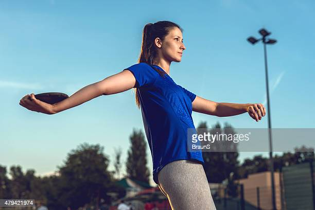 Young female athlete about to throw a discus.
