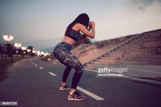 young female athlete doing squats on running path - bunda imagens e fotografias de stock