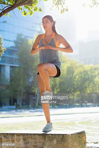 Young female athlete doing stretching exercise in city park